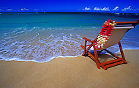 Beach chair draped with a colorful plumeria flower lei on a sunny tropical Hawaiian white sand beach
