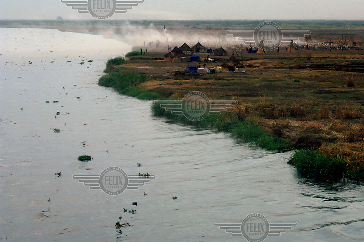 Huts and a herd of cattle on a Dinka settlement along the River Nile.