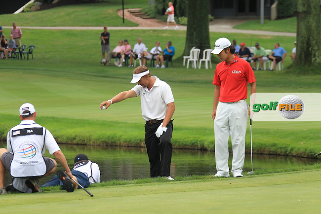 Kevin Na's (USA) caddy holds onto Martin Gray's legs, Joost Luiten's (NED)  caddy, as Joost prepares to drop a ball at the water's edge beside the 16th green during Sunday's Final Round of the 2012 World Golf Championship Bridgestone Invitational at The Firestone Country Club, Akron, Ohio, USA 5th August 2012 (Photo Eoin Clarke/www.golffile.ie)