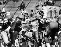 Oakland Invaders ...rush on QB Landry, by #92 Tim Moore,#73 Dave Browning and #91 Monte Bennett..Photo May 13,1984 by<br />