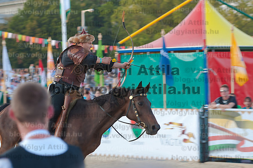 Equestrian in ancient Hungarian outfit rides his horse while aiming with an arch during the National Gallop held on Heroes' Square in Budapest, United Kingdom on September 17, 2011. ATTILA VOLGYI
