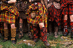 The Clan, Scotland, a group who spend weekends at a camp in Glen Croe, recreating the life of a Scottish clan before the defeat of Bonnie Prince Charlie at the Battle of Culloden in 1746. Different tartans are worn for camouflage at different seasons. The kilt secured with three strong leather belts, stays in place for several days. It can be worn in a variety of styles depending on what the wearer will be doing, from hunting to sleeping. 1989 1980s UK.