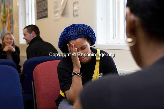 A prisoner speaks with a friend during visiting time. HMP Send, closed female prison. Ripley, Surrey.