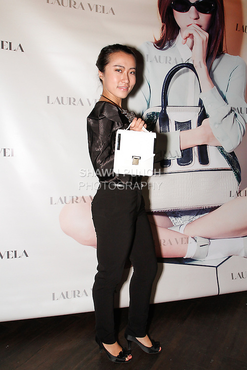 Michelle Zhao poses with Laura Vela handbags during the Laura Vela handbag installation at No. 8 in New York City on September 17, 2013.