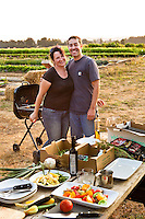 Farmers, potrait of Leslie and Manudel Recio as they prepare outdoor supper picnic grill with fresh farm vegetables, Viridian Farms