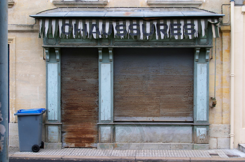 An old closed down shoe shop with rusty window shutters, a word out sun shade and a gray grey dust bin garbage tin with a blue cover. Commerce has seen better days. Business could be better. No customers here. Footfall foot fall is elsewhere. Branne Entre-deux-Mers Bordeaux Gironde Aquitaine France