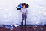 Young man with an umbrella waiting against a wall as bubbles rain on him