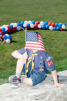A cub scout holds an American flag in front of his face before the 4th of July Parade in Amherst, New Hampshire, on Thu., July 4, 2019.