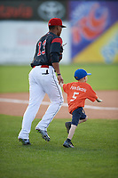 "Batavia Muckdogs left fielder Jhonny Santos (13) runs out to the field with a young ""Star of the Game"" before a game against the West Virginia Black Bears on June 24, 2017 at Dwyer Stadium in Batavia, New York.  The game was suspended in the bottom of the third inning and completed on June 25th with West Virginia defeating Batavia 6-4.  (Mike Janes/Four Seam Images)"
