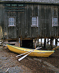 Lunenburg County, Nova Scotia<br /> Yellow dory and oars rest at the tide line below the weathered Dory Shop on the Lunenburg waterfront