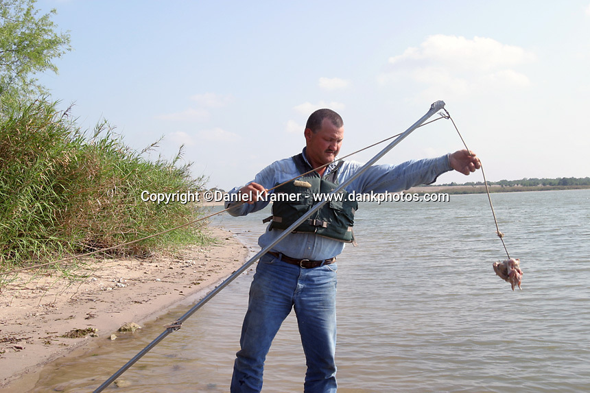 Larry Janik prepares a hook and line to capture an alligator.