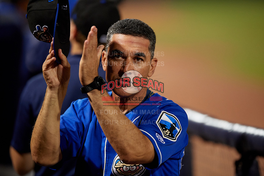 Biloxi Shuckers coach Mike Guerrero (13) applauds for a military recognition break during a Southern League game against the Pensacola Blue Wahoos on May 3, 2019 at Admiral Fetterman Field in Pensacola, Florida.  Pensacola defeated Biloxi 10-8.  (Mike Janes/Four Seam Images)