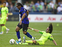 Manchester United midfielder Anderson, left, escaps the slide tackle Seattle Sounders FC midfielder Mauro Rosales during play at CenturyLink Field in Seattle Wednesday July 20, 2011. Manchester United won the match 7-0.