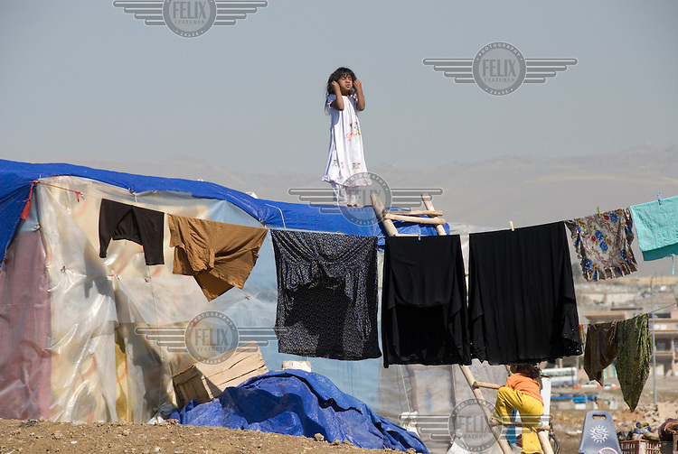 A child on the roof of her home in the Qawala camp for displaced persons, where 136 families from accross the country are housed.