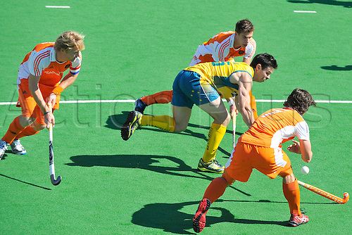 02.12.2012 Melbourne, Australia. Trent Mitton of Australia attempts to outrun three Dutch defenders during the Men's Hockey Champions Trophy from the State Netball Hockey Centre.