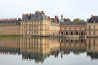 The Cour de la Fontaine with its Ulysses fountain, 16th century, and the Carp Pond in the foreground, Chateau de Fontainebleau, France. The courtyard is bordered to the west by Gabrielís Grand Pavilion, 1750, the Queen Motherís Wing, 1558-65, to the north by the wing of the Francois I Gallery, 16th, 17th & 19th century, and Primaticcioís Belle-Cheminee Wing, 1565-70. The Palace of Fontainebleau is one of the largest French royal palaces and was begun in the early 16th century for Francois I. It was listed as a UNESCO World Heritage Site in 1981. Picture by Manuel Cohen