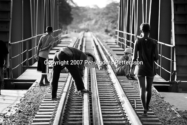 DONDO, ANGOLA APRIL 3: An unidentified Chinese railway worker flirts with an Angolan woman while drilling holes on the newly put tracks on April 3, 2007 in Dondo, about 200 kilometers outside Luanda, Angola. Chinese companies are building and upgrading two different railways in Angola, and this part is about 500 kilometers long. All the special equipment has been shipped from China and hundreds of workers live in military style road camps. They are moved as the tracks are laid down. Tens of thousands of Chinese has come to Africa the last years to work in infrastructure projects and businesses. Chinese companies are often the lowest bidders for contracts, pricing out the more expensive European companies. The Chinese people often live where they work and rarely interact with the local population. Most Chinese don't speak English and they are mostly staying in the compounds cooking their Chinese food. .(Photo by Per-Anders Pettersson)..