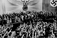 "Berlin, March 1938 - Title: Hitler accepts the ovation of the Reichstag after announcing the ""peaceful"" acquisition of Austria. It set the stage to annex the Czechoslovakian Sudetenland, largely inhabited by a German-speaking population."