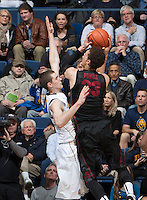 David Kravish of California tries to block the ball against Dwight Powell of Stanford during the game at Haas Pavilion in Berkeley, California on February 5th, 2014.  Stanford defeated California, 80-69.