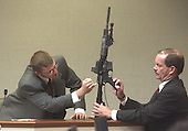 Brendan Shea, a United States Federal Bureau of Investigation (FBI) DNA expert, points to the Bushmaster rifle used in the sniper shootings as Prince William County (Virginia) Assistant commonwealth attorney James Willett holds the weapon during his testimony in the trial of sniper suspect John Allen Muhammad in courtroom 10 at the Virginia Beach Circuit Court in Virginia Beach, Virginia on November 5, 2003. <br /> Credit: Dave Ellis - Pool via CNP