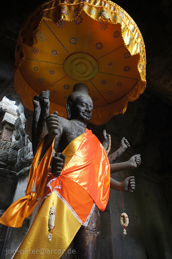 vishnu statue with saffron umbrella,  entrance of main temple Angkor Wat, right wing side, Cambodia, August 2011. Main temple Angkor what was originally dedicated in 12th century to Lord Vishnu, later became a famous destination of pilgrimage for buddist also