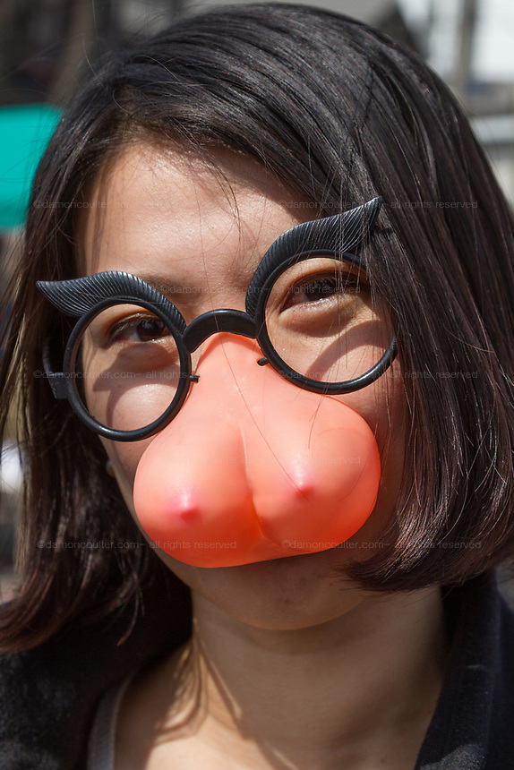 A Japanese woman wearing joke spectacles with a pair of breasts on them during the Kanamara matsuri or festival of the Steel phallus Kawasaki Daishi, Kawasaki, Kanagawa, Japan. Sunday, April 2nd 2017. The Kanamara Penis festival takes place on the first Sunday of April and celebrates the local legend of a penis eating demon who was defeated after being tricked into biting a steel phallus. The festival is popular with Japan's gay community and now uses its notoriety to raise money for HIV and AIDS charities. It is also wildly popular with foreign and Japanese.tourists.