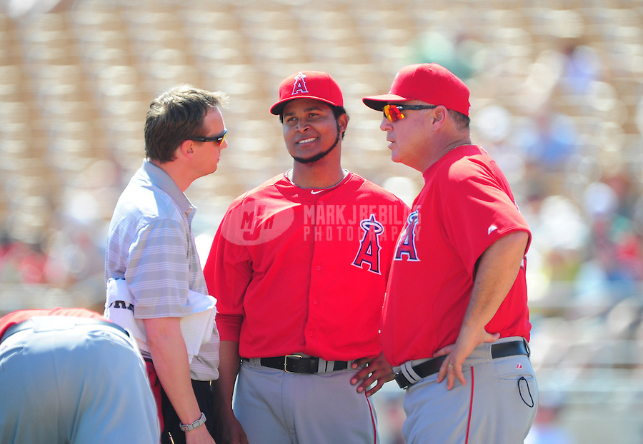 Mar. 14, 2012; Phoenix, AZ, USA; Anaheim Angels pitcher Ervin Santana (center) talks with a team trainer and manager Mike Scioscia (right) after being hit by a line drive in the second inning against the Chicago White Sox at The Ballpark at Camelback Ranch. Mandatory Credit: Mark J. Rebilas-