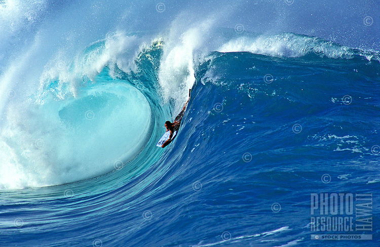 A body boarder surfs a huge perfectly curled wave on the north shore of Oahu.