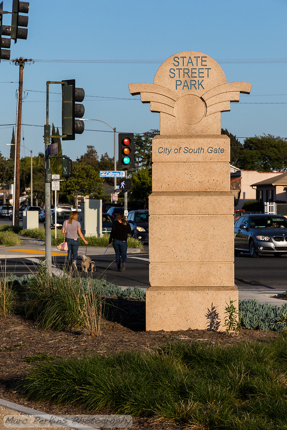 The eastern entrance sign to State Street Park, with landscaping visible in front and walkers crossing in the crosswalk with a walk signal and green light.