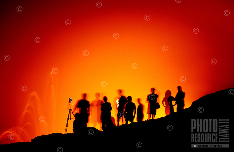 Silhouettes of several people and a camera tripod against a glowing orange and red sky from the lava going into the sea off the coast of the Big Island of Hawaii.