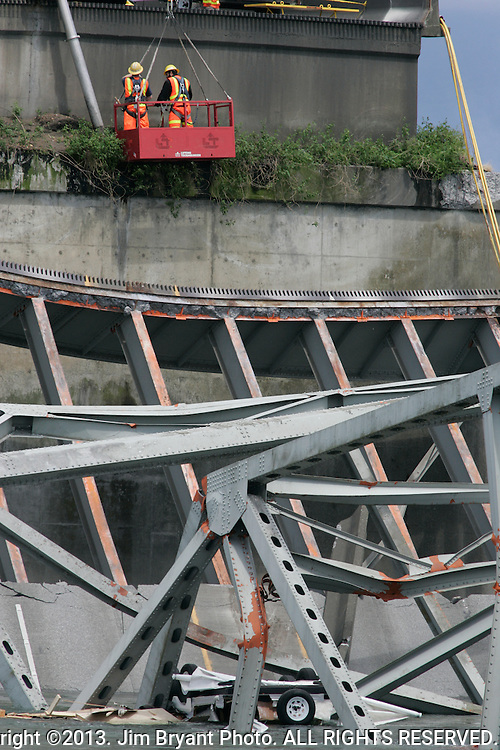 A car and a truck rest in the water underneath the Northbound I-5 Bridge in Mt. Vernon on May, 24, 2013. A truck hauling an oversized load struck an overhead bridge girder on the I-5, a major interstate between Seattle and Canada, sending a section of the span and two vehicles into the Skagit River on Thursday of the north part of the four-lane Interstate 5 bridge near Mount Vernon, about 60 miles north of Seattle and 40 miles south of the Canada border, and disrupted travel in both directions.   ©2013. Jim Bryant Photo. All Rights Reserved.