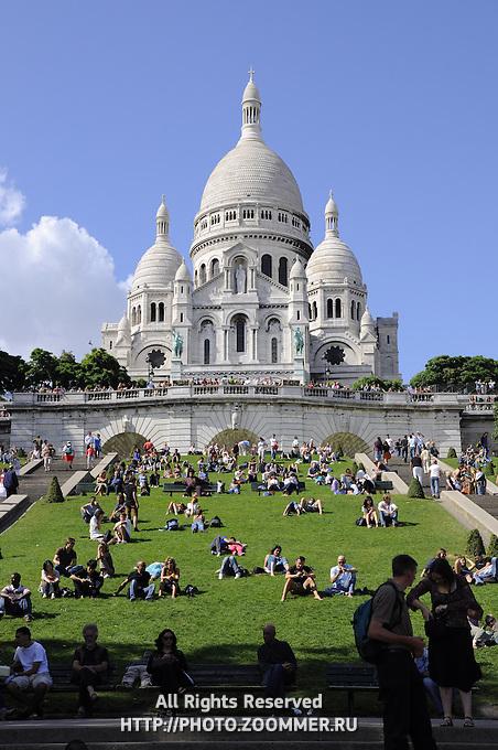 Montmartre, Paris. Basilica Sacre Coeur with tourists on green lawn