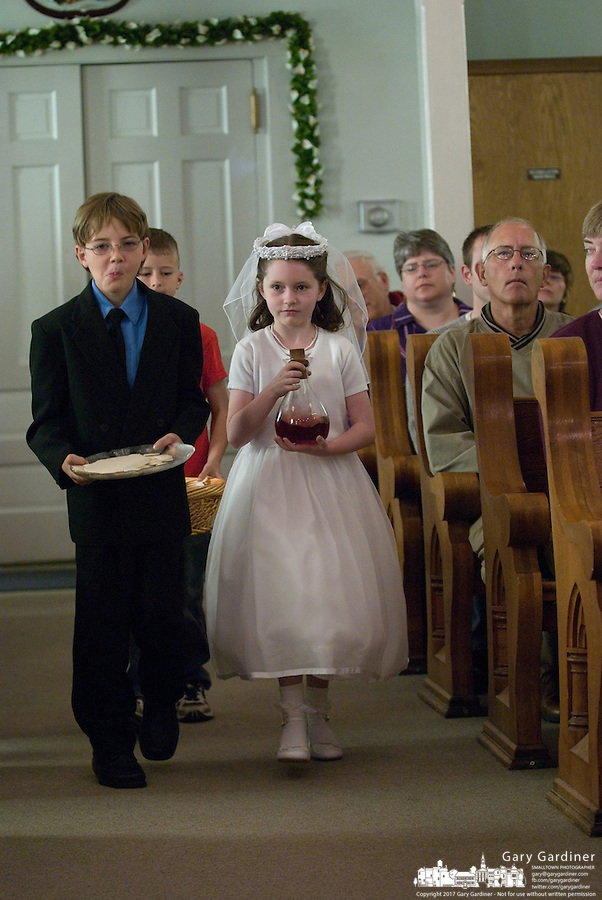 A young girl and boy bring up wine and bread for their first communion sacrament at a Catholic church in Johnstown, OH.<br />