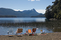 The Seven Lakes Route, one of Argentina's classic scenic drives, in the Parque Nacional Nahuel Huapi, passes through thickly forested mountain valleys and actually past more than seven wild lakes. This is one of those lakes, Lago Espejo, where a small camp site has been set up. Some families have been enjoying the wonderful view and have briefly retreated to the shade.
