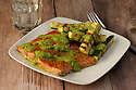 Salmon fillet grilled and served with pesto sauce and zucchini sticks