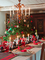 A cheerfully laid Christmas table with a striped table runner and woven napkins