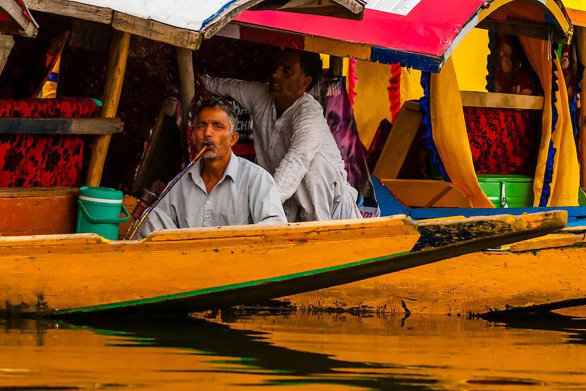 Man smoking a hookah pipe on board a shikara (boat) on Dal Lake in Srinagar, Kashmir, Jammu and Kashmir State, India.