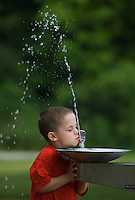 Young boy in red shirt drinks from water fountain with high spray.