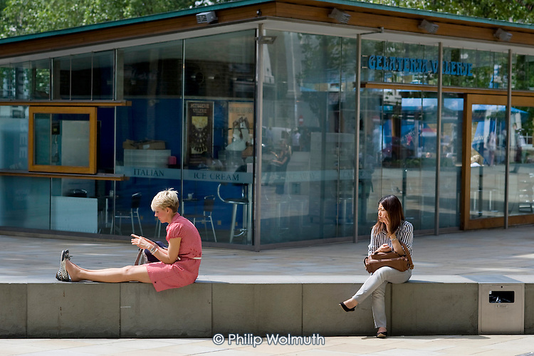 Two women using mobile phones in the King's Road, Chelsea, London.