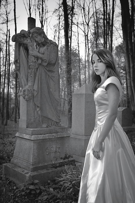 A Teen Bride in a wedding dress in a graveyard at dusk