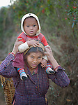 A woman carries her son in Makaising, a village in the Gorkha District of Nepal that suffered from a devastating 2015 earthquake.