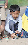 A boy plays marbles in the Cambodian village of Pheakdei.
