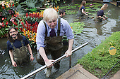 London, UK. 16 March 2015. Carlos Magdalena and Boris Johnson. Mayor of London Boris Johnson puts on waders and joins Kew horticulturist Carlos Magdalena, apprentices and diploma students in the pond to plant young Victoria amazonica waterlilies, colourful hybrid waterlilies, in the Princess of Wales Conservatory at the Royal Botanic Gardens, Kew.