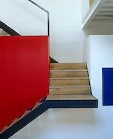 A cantilevered staircase has wooden treads and a metal frame and is enhanced by a red wall