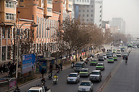 Traffic moves along Renmin Lu (People's Street) in the center of Kashgar, Xinjiang, China.