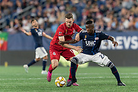 FOXBOROUGH, MA - AUGUST 31: Patrick Mullins #13 of Toronto FC and Luis Caicedo #27 of New England Revolution battle for the ball during a game between Toronto FC and New England Revolution at Gillette Stadium on August 31, 2019 in Foxborough, Massachusetts.
