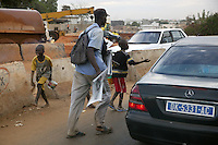 Senegal. Dakar. Early morning in town center, cars are stopped in a traffic jam. Children are begging for money while a man sells newspapers on the road. 04.12.09  © 2009 Didier Ruef