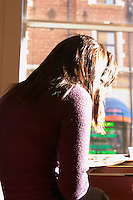 A young woman sitting in a cafe with a cup of coffee reading a newspaper in a purple sweater. strong afternoon light Stockholm, Sweden, Sverige, Europe