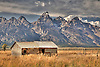A rustic cabin left over by Mormon settlers stands before the Grand Tetons in Jackson Hole, Wyoming