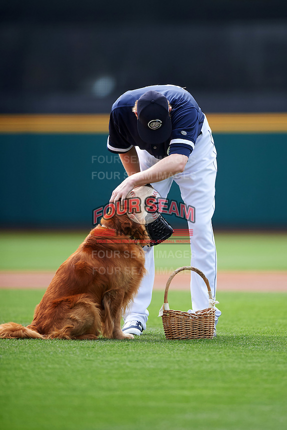 Columbus Clippers starting pitcher Ross Detwiler (41) pets Jake the Diamond Dog who brought out the game ball before a game against the Lehigh Valley IronPigs on May 12, 2016 at Huntington Park in Columbus, Ohio.  Lehigh Valley defeated Columbus 2-1.  (Mike Janes/Four Seam Images)